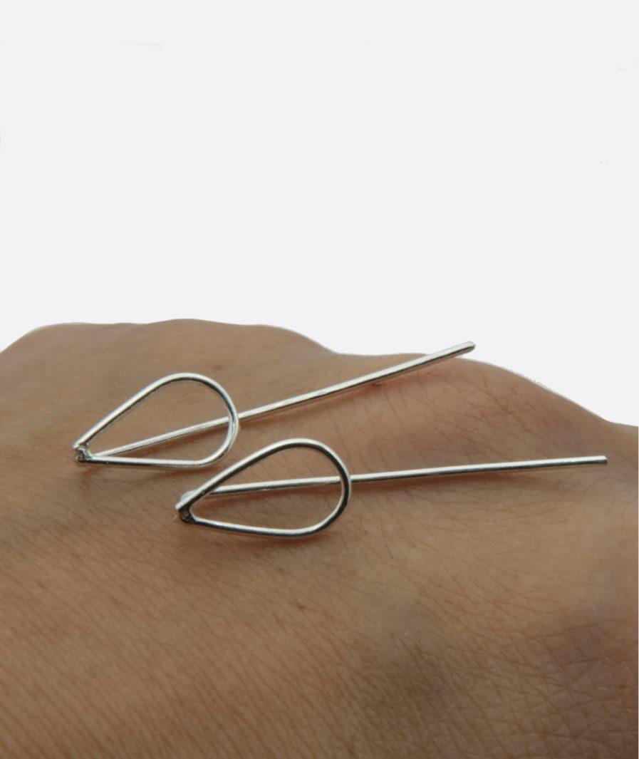 finos pendientes minimalistas sobre el dorso de una mano. forma de lágrima