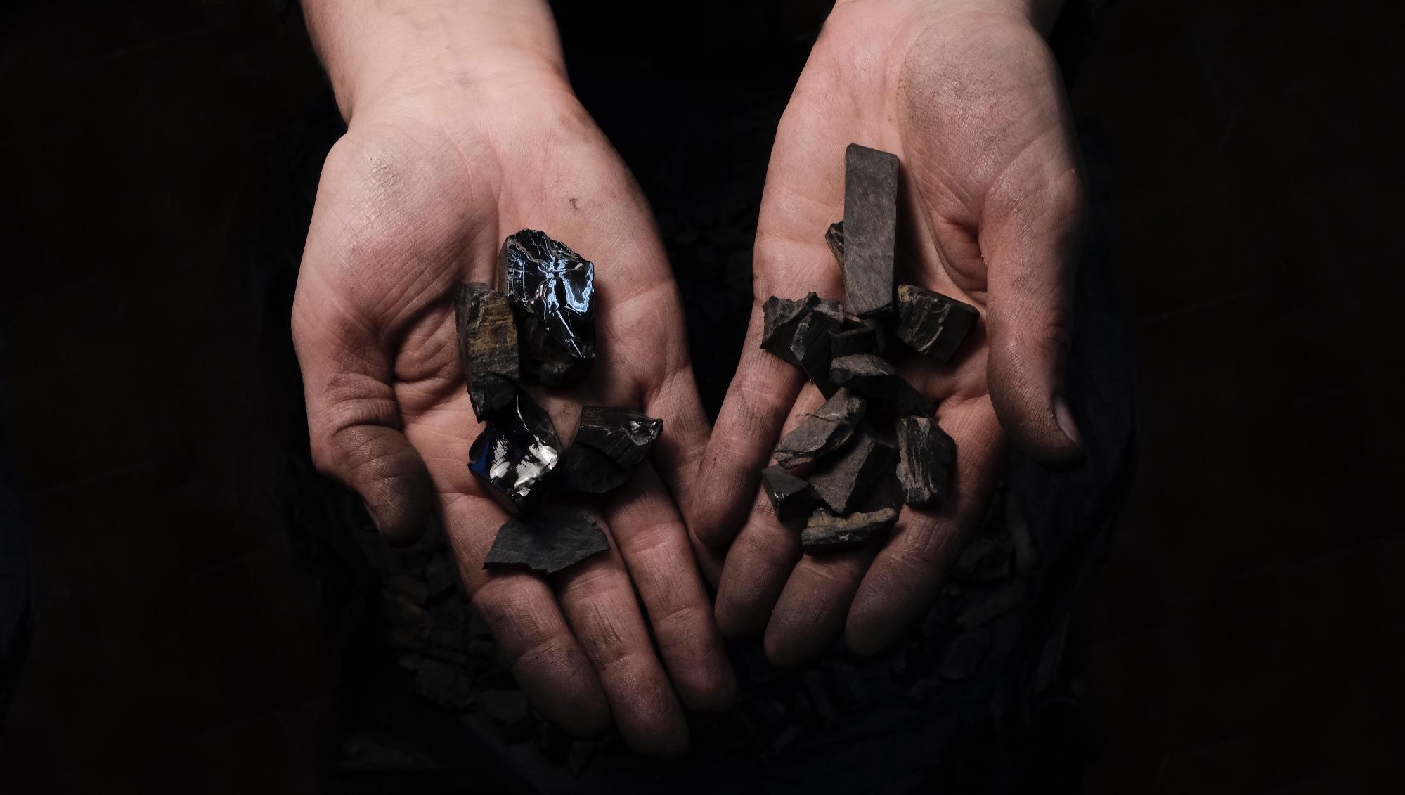 manos manchadas por el pulido de joyas en la orfebrería con trozos de azabache asturiano en bruto